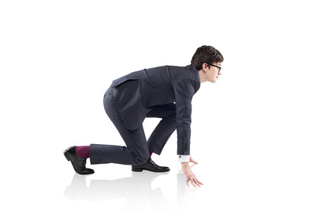 readiness: A young handsome businessman wearing a suit and glasses at crouch start ready to run. Concept of readiness
