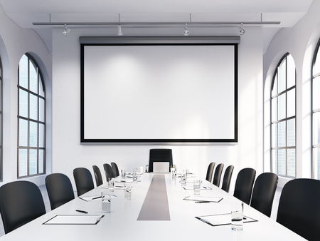 meeting agenda: Light spacious meeting room in office building, big windows on two sides, big white table and black leather armchairs around, lamps above. White blank screen on the back wall. Concept of negotiations Stock Photo