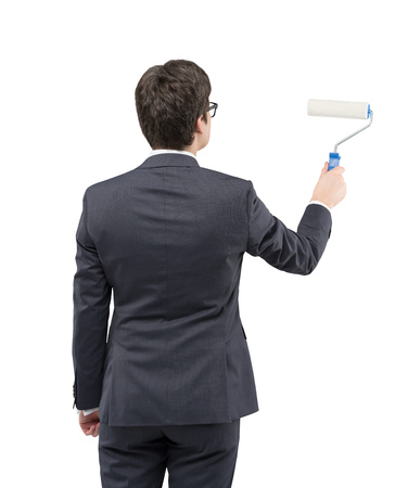 new start: A young businessman wearing glasses starting to draw something on a blank white wall with a roller, Back view. Concept of a new start. Stock Photo