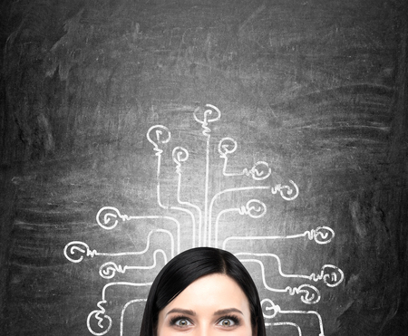 smart woman: Young woman looking in front, labyrinth with each line ending in a bulb painted on the blackboard behind her. Front view. Concept of making choice. Stock Photo