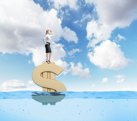 afloat: Young businesswoman standing confidently on  huge gold dollar sign afloat and looking forward, sea background, blue sky, Concept of wealth. Stock Photo