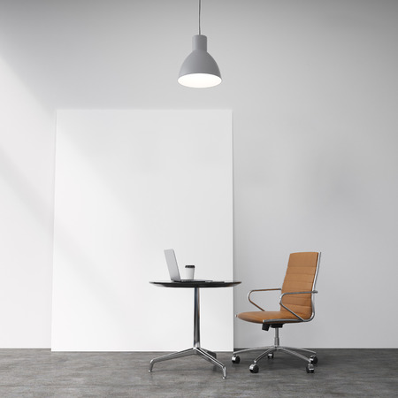 A brown leather castor chair at a small table with a laptop and a glass of coffee on it, a lamp above. Concrete background with a white board. Concept of individual work.