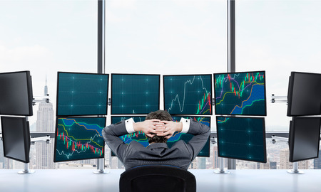 wallstreet: Rear view of a relaxing trader who is sitting in front of a trading station which consists of eight screens with financial data. A concept of forex trading.