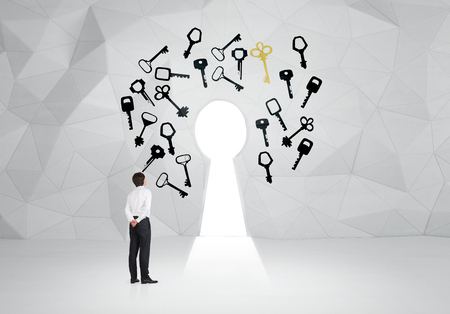 key hole: Young man with hands back standing in front of a key hole with different keys painted around. White background.  Concept of finding a solution.