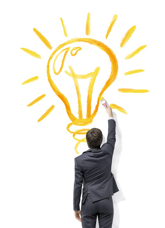 bright light: A businessman painting a huge shining yellow bulb on the white background. Back view. Concept of a new idea. Stock Photo