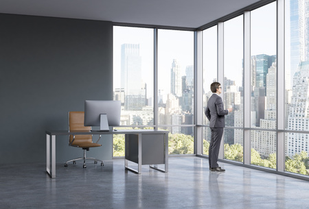 looking through: Young businessman standing with a glass of coffee and looking through the window in a spacious office in a business centre in New York. Side view. Concept of earning work.