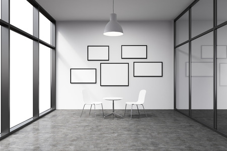 talks: Empty office in a skyscraper, French window to the left, small blank frames on the white wall. A small white table and two white chairs at the wall, lamp above. Concept of talks. Stock Photo