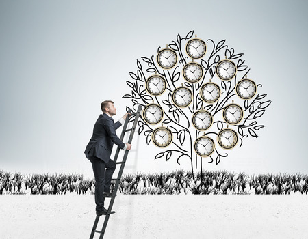 Young businessman climbing a drawn tree with clocks instead of leaves via ladder. Gray background. Concept of timing