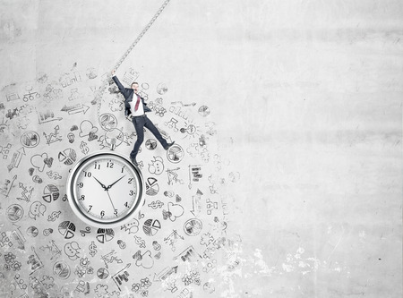 Businessman with his right hand up standing on the clock with his right foot.  Concrete background partly with small business icons. Concept of work.