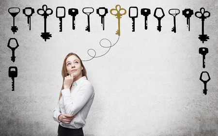 solution: Young woman with hand to the chin looking up in search of the right solution which are presented as keys around her. Concrete background. Concept of finding a solution.