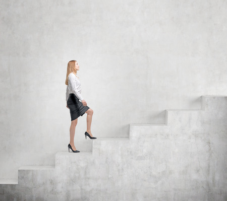 steadily: Young businesswoman going up a a concrete stairs steadily along a concrete wall. Concept of career growth. Stock Photo