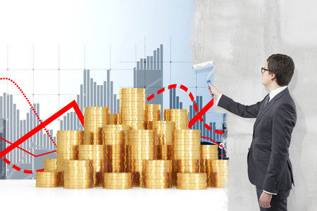 Young businessman painting grey bar charts and red graphs on a white wall with a roller, heaps of coins in front. Side view. Concept of financial profit.