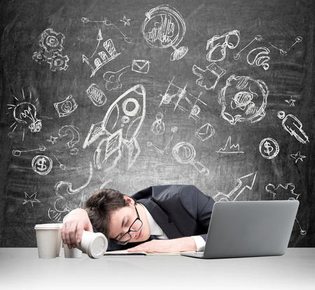 fulfilment: Young man fell asleep in front of laptop, face on the note book, inverted glass of coffee in hand, several glasses aside. Blackboard with pictures at the background. Concept of overworking
