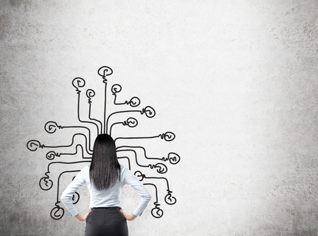 Young businesswoman with hands on hips looking at a labyrinth with each line ending in a bulb painted on the concrete wall in front of her. Back view. Concept of making choice.