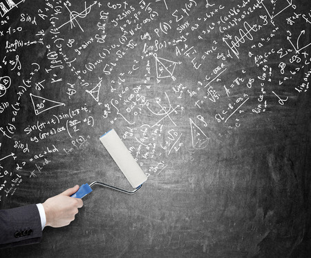 new ideas: Hand painting on a blackboardl with a roller covering it with mathematic signs, graphs, notes. Concept of giving new ideas Stock Photo