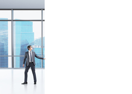 affluence: Young businessman pulling a white panel trying to close a part of an office in a Singapore skyscraper. Concept of new organization Stock Photo