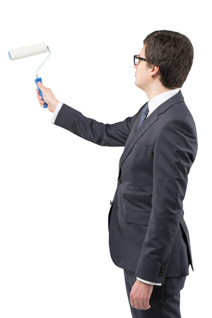 new start: A young businessman starting to draw something on a blank white wall with a roller, Side view. Concept of a new start.