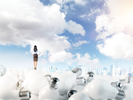 woman standing back: Young woman with hands on hips standing on huge scattered bulbs. Blue sky at the background. Back view. Concept of new ideas.