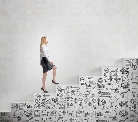 steadily: Young businesswoman going steadily up a a concrete stairs with drawn business icons on it along a concrete wall. Concept of career growth.