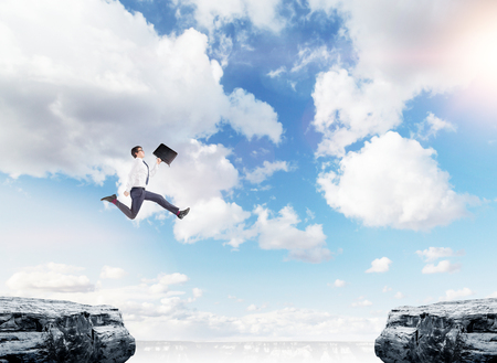 bridging the gap: A young businessman with a folder in his hand jumping between two cliffs, blue sky at the background. A concept of bridging the gap.