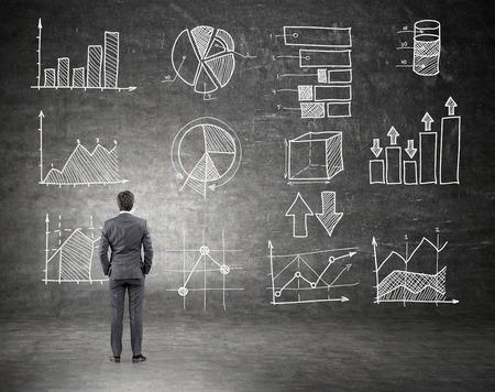 dollaro: Giovane uomo d'affari in piedi con le mani in tasca e guardando la parete nera con tabelle e grafici. Vista posteriore. Concetto di guadagnare soldi