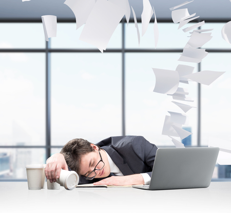 overworking: Businessman fell asleep in front of laptop, face on the note book, inverted glass of coffee in hand, several glasses aside. Paper flying around. Window at the background. Concept of overworking