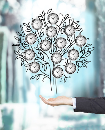 A hand holding a drawn tree with clocks instead of leaves. Blurred background. Concept of timing Stock Photo