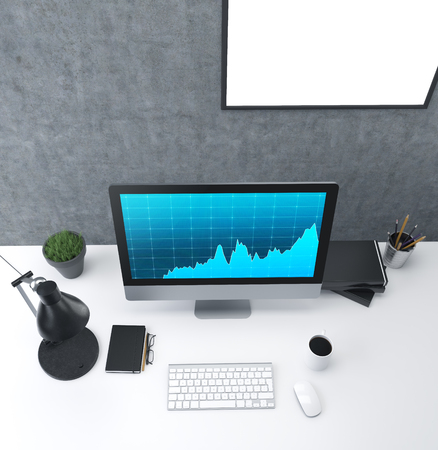 Workplace: a computer with graphs on the screen, lamp, plant, organizer and glasses, cup, mouse, three datebooks and  pencils; white blank frame on the wall. Top view. Concept of work. Stock Photo