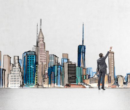 earing: Young businessman painting a picture of New York city centre on a wall with colours and a brush. Concept of dreaming.