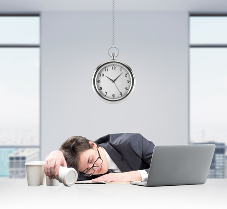 overworking: Businessman fell asleep in front of laptop, face on the note book, inverted glass of coffee in hand, several glasses aside. Pocket watch hovering above. Concept of overworking
