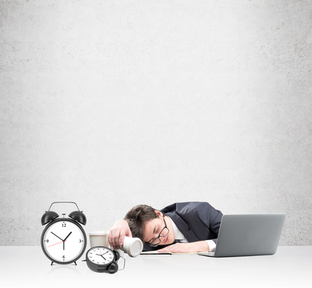 overworking: Young businessman fell asleep in front of the laptop, his face on the note book, inverted glass of coffee in hand, several empty glasses aside. Two alarm clocks in front. Concept of overworking Stock Photo