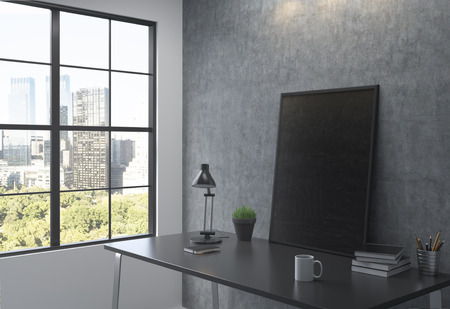 datebook: A big black frame on the table leaning on the grey wall, a lamp, a pot with a plant and a datebook on the table, window with New York view to the left. Concept of work. Stock Photo