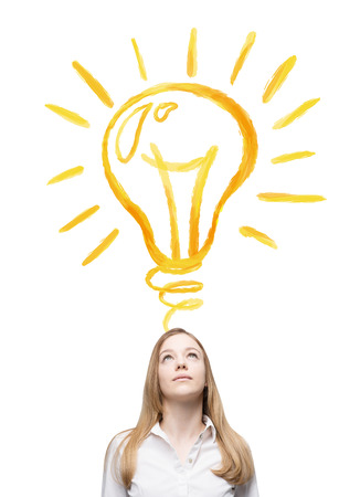 yellow bulb: A young businesswoman looking at a huge shining yellow bulb on the white background over her head. Front view. Concept of a new idea. Stock Photo