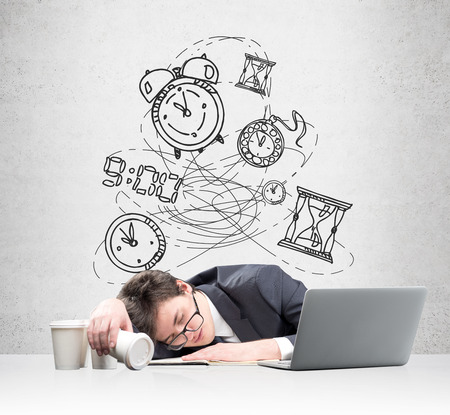 overwork: Young businessman fell asleep in front of the laptop, face on the note book, inverted glass of coffee in hand, several empty glasses aside. Several drawn clocks at the background. Concept of overwork Stock Photo