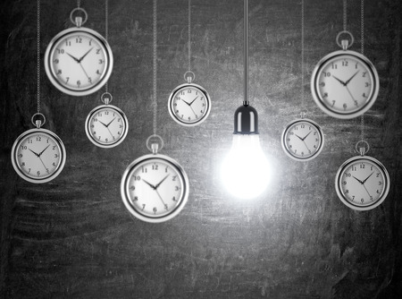 smart goals: Several pocket watches hanging from th ceiling, one bulb among them. Black background. Concept of time and new ideas.