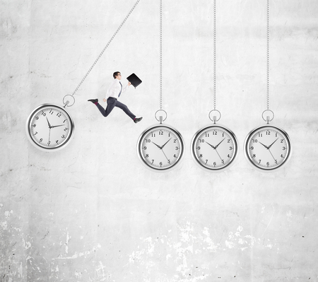 coping: Young businessman with a folder in hand jumping from one hovering pocket watch to another, concrete background. Concept of coping with the task. Stock Photo
