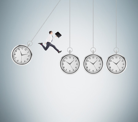 coping: Young businessman with a folder in hand jumping from one hovering pocket watch to another, light grey background. Concept of coping with the task.