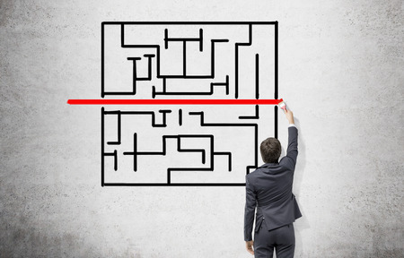 labirinth: Young businessman painting a black labyrinth on the concrete wall with a horizontal red line in the middle. Back view. Concept of finding a solution.