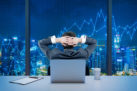 trade: Rear view of a relaxing trader who is sitting in front of a window, laptop behind him. Night New York view. Graphs at the background. A concept of forex trading.