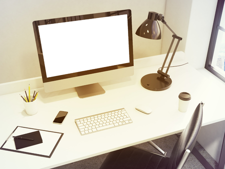note pad and pen: workplace in the corner, blank computer, keyboard, mouse, smartphone, lamp, note pad, pen, pencil glass, coffee on the table, chair in front, light from the window to the right. Concept of work