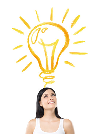 yellow bulb: A pretty young smiling woman looking at a huge shining yellow bulb on the white background over her head. Front view. Concept of a new idea. Stock Photo
