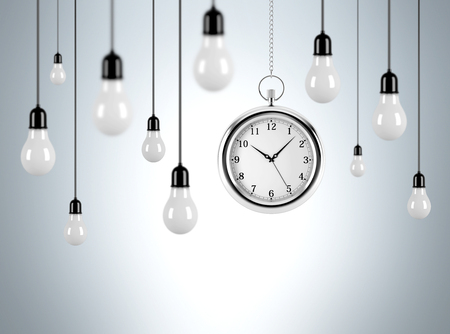 smart goals: Several bulbs hanging from th ceiling, one pocket watch among them. Grey background. Concept of time and new ideas.