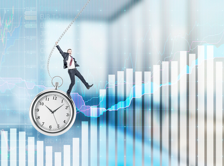 streamlining: Businessman with his right hand up standing on the clock with his right foot and swinging. Blurred background with charts and graphs. Concept of timing.