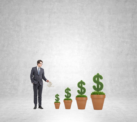 Young businessman with one hand in pocket holding a watering can pouring water on plants in dollar shape in four pots from big to small so that it grows. Concrete background. Concept of money growth Stock Photo
