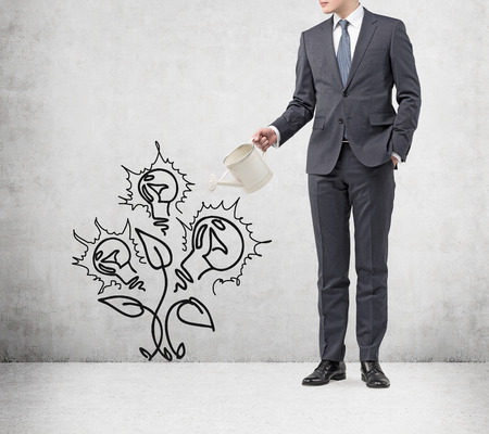 Young businessman with one hand in pocket holding a watering can pouring water on a drawn plant with ideas instead of flowers. Concrete background. Concept of money growth Stock Photo
