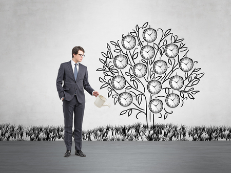 Young businessman with one hand in pocket holding a watering can pouring water on a drawn tree with clocks instead of leaves. Concrete background. Concept of timing Stock Photo