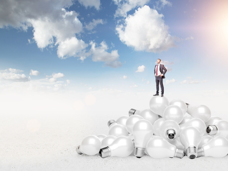 way out: Young man with hands in pockets standing on a heap of huge scattered bulbs, proud of himself. Blue sky at the background. Concept of new ideas. Stock Photo
