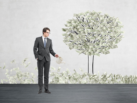 affluence: Young businessman with one hand in pocket holding a watering can pouring water on a drawn tree with dollars instead of leaves. Some dollar grass. Concrete background. Concept of money growth Stock Photo