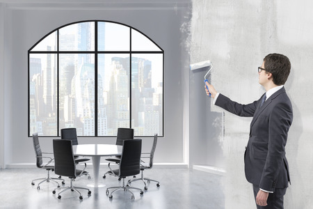 reorganization: Young businessman covering a picture of a meeting room for six people in New York with grey paint using a roller. Concept of reorganization.