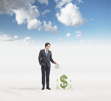 affluence: Young businessman with one hand in pocket holding a watering can pouring water on plants in dollar shape so that it grows, blue sky at the background. Concept of money growth